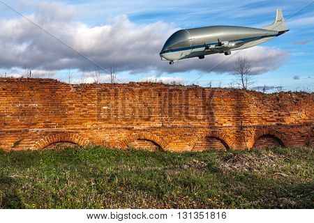 NASA Super Guppy, a wide-bodied cargo aircraft in the blue sky over a red brick wall. Elements of this image furnished by NASA. Collage.