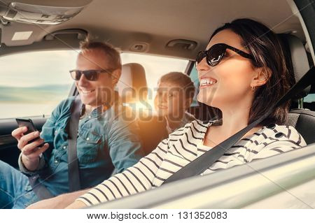 Happy family riding in a car .