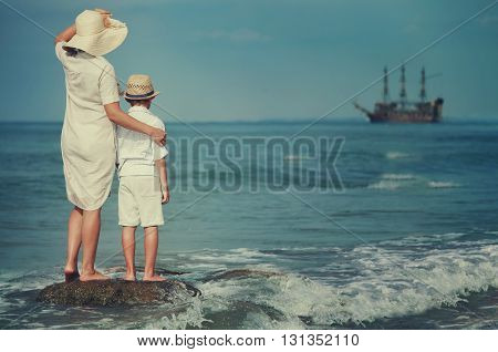 Mother with son look together on the ship in the sea