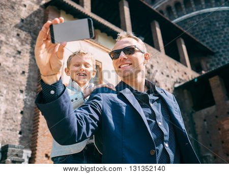 Father with son take a selfie photo in old castle