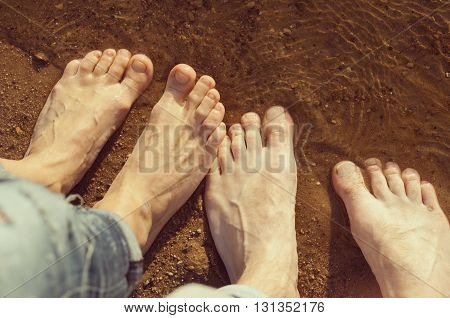 woman's and man's feet standing on the sand