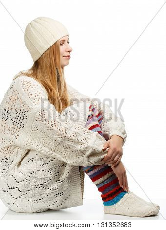 Young beautiful smiling woman with long blonde hair siting in white knitted sweater cap and striped gaiters isolated on white background in hugging knees pose