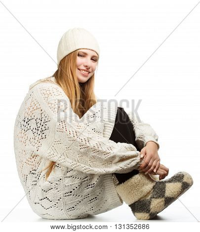 Young beautiful woman siting in white sweater and cap isolated on white background
