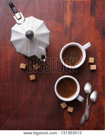 Two cups of espresso with pieces of cane sugar and Italian  coffee maker on old  wooden table.