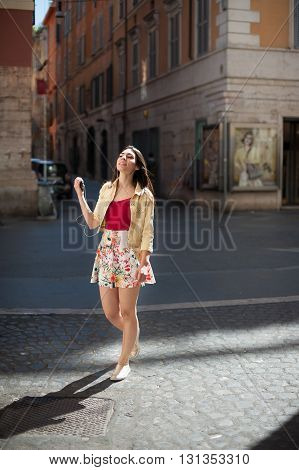 Young smiling cheerful woman listening music with headphones while walking in the city street