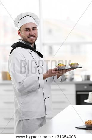 Male chef holding freshly made tarts