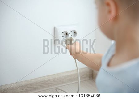 Little boy playing with wire and plug