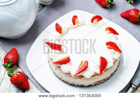 Strawberry cheesecake with fresh strawberries and whipped cream frosting.