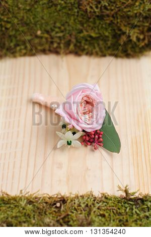 Beauty of colored flowers. Bridal accessories. Close-up bunch of florets. Details for marriage and for married couple. Wedding bonbonniere for the groom on wooden background