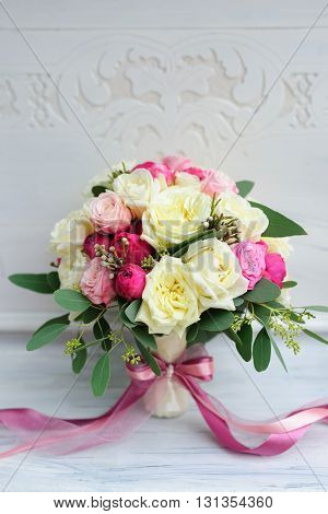 Beauty of colored flowers. Bridal accessories. Close-up bunch of florets. Details for marriage and for married couple. Wedding bouquet with peonies, roses on the white background