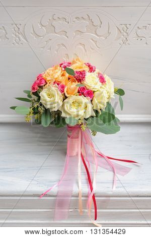 Beauty of colored flowers. Bridal accessories. Close-up bunch of florets. Details for marriage and for married couple. Wedding bouquet with roses n the white background