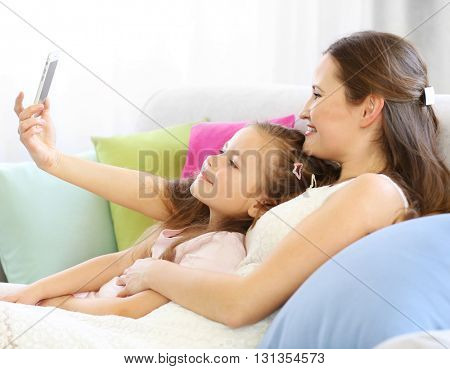 Mother and daughter making selfie indoors