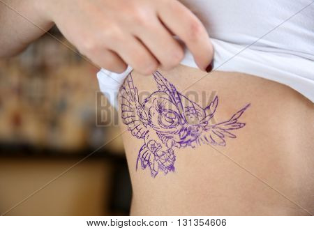Female body with bird drawing, closeup