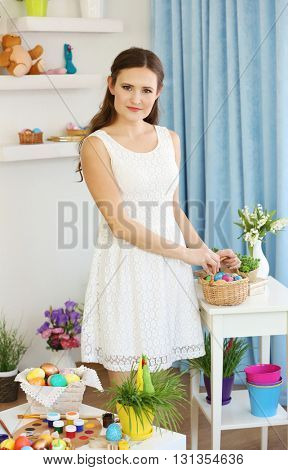 Young woman with Easter eggs and flowers indoors
