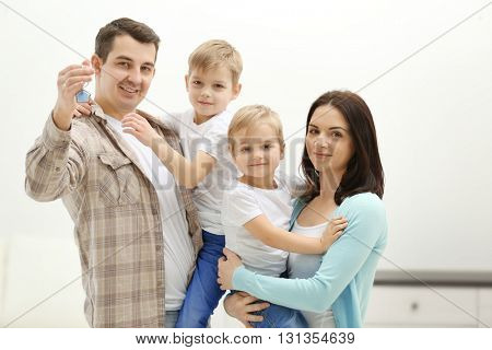 Happy family with key in new house, indoor