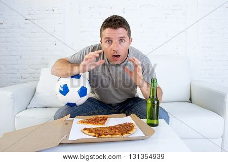 young man alone holding ball in stress watching football game on television sitting at home living room sofa couch with pizza box and beer bottle enjoying the match looking excited and shocked