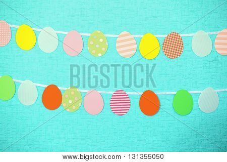 Cutout Easter eggs handing on turquoise textured background