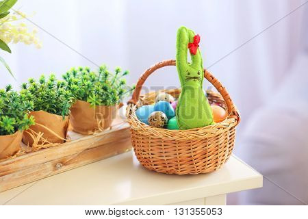 Easter eggs in wicker basket and plant on wooden nightstand, indoors