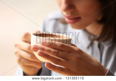 Young woman in cafe holding cup of coffee
