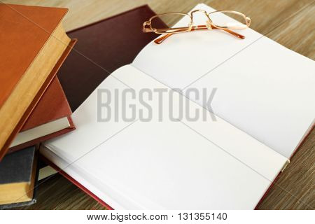 Glasses and open book on wooden background