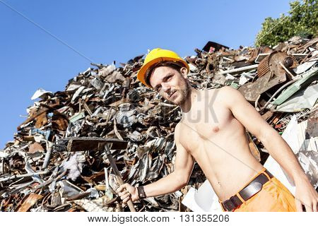 young worker in a junkyard shoveling iron scrap