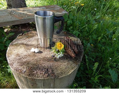 Thermomug of fragrant tea on the stump outdoors