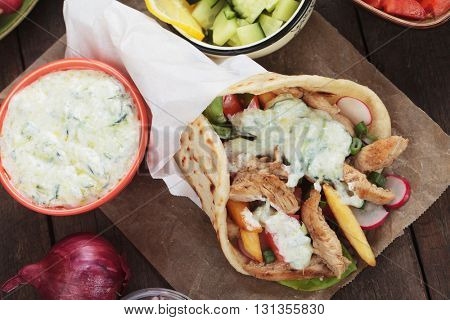 Gyros, greek pita bread wrapped sandwich with meat slices, tzatziki and vegetables