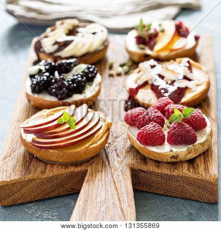 Variety of bagels with different toppings for breakfast on a board