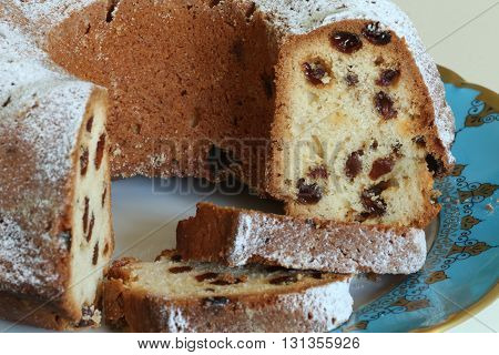 sponge cake with raisins with golden crust dusted with icing sugar close to