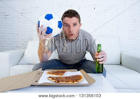 young man alone holding ball and beer bottle watching football game on television sitting at home living room sofa couch with pizza box enjoying the match looking nervous and excited