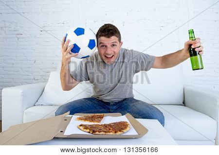 guy alone at home holding ball and beer bottle watching football game on television sitting on living room sofa couch with pizza box celebrating goal or victory gesturing crazy
