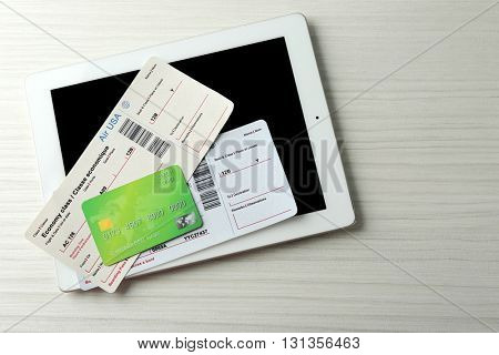 Tablet with credit card and flight tickets on light wooden table