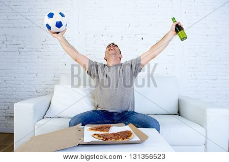 young man alone holding ball and beer bottle watching football game on television sitting at home living room sofa couch with pizza box celebrating goal or victory gesturing crazy