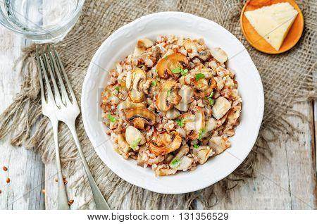Mushrooms cheese buckwheat on white wood background.