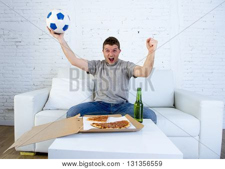 young man alone holding ball watching football game on television sitting at home living room sofa couch with pizza box and beer bottle celebrating goal or victory gesturing crazy
