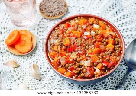 Vegan green lentil tomatoes stew on wooden background