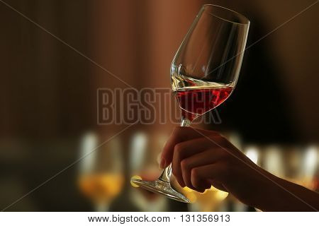 Woman holding a glass of red wine, close up