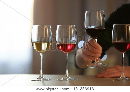 Man holding a glass of red wine at the table