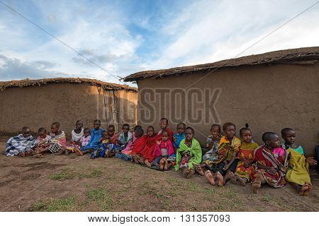 MAASAI VILLAGE KENYA - JANUARY 2 2015: Children of maasai tribe seat on the ground near their houses. Problems of African children are very sharp nowadays and have actual humanitarian significance