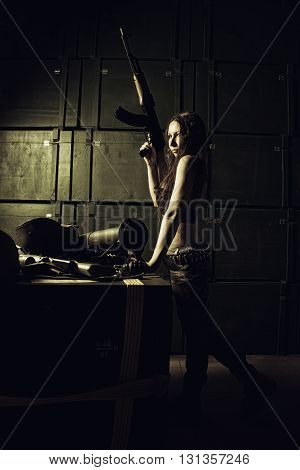 Brave serious girl posing with automatic rifle