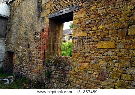 Old wall in stones with a frame of empty window and a shore.