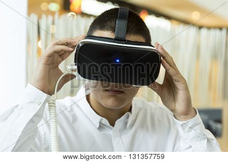 Sofia Bulgaria - May 13 2016: An young man experiences virtual reality mounting a (VR) headsets (glasses) rig on his head during an exhibition for new technologies.