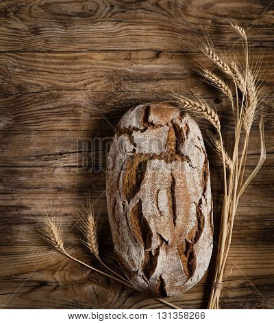 Top view of loaf of bread decorated with ears of wheat on an rustic wooden table.