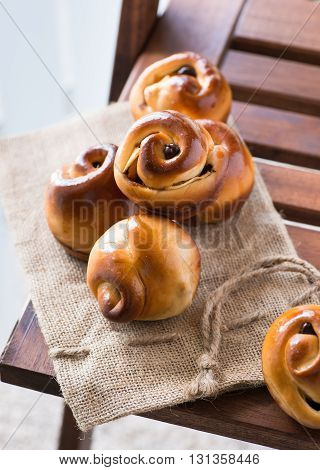 Homemade buns with chocolate and apples on the wooden background. Selective focus