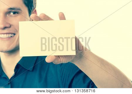 Advertisement concept. Young handsome man holding blank piece of paper. Smiling guy showing empty ad. Filtered.