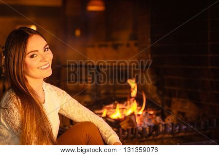 Joyful happy woman relaxing resting at fireplace. Young girl heating warming up. Winter at home.