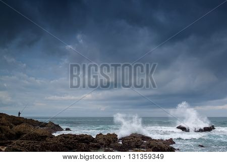 Brave fisherman fishes on the sea. The violent storm.