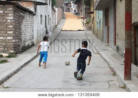 Magdalena Peru - May 18 2016: Two young boys practice soccer in front of street full of dry corn kernels in Magdalena Cajamarca Peru on May 18 2016