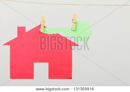 Red house with green key hang on laundry line on grey background. Selling and buying home concept.