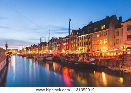 Colorful houses in Copenhagen old town with boats and ships in the canal in front of them. Long exposure shot at night. Travel and architecture concepts